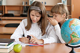 Two girls sitting at school desk with mobile phone