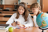 Two girls are using mobile phone with interest