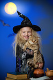 Girl dressed up as witch in night with cat