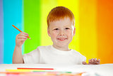 Red-haired adorable boy drawing with orange pencil on rainbow ba