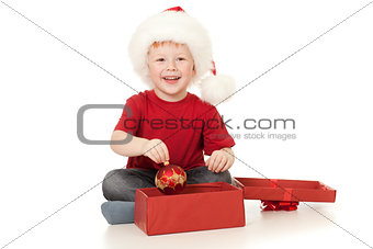 Adorable boy in Santa hat opening christmas gift in red box isol