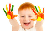 Adorable red-haired boy with focus on hands painted in bright co