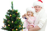 Father helps daughter decorate Christmas tree