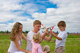 Happy family launching toy aircraft model together