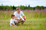 Father and son launch plane model in summer field