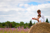 Father and son have fun with toy aircraft model on haystack
