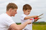 Father and son have fun with toy aircraft model in park