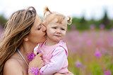 Mother kissing daughter in meadow outdoor