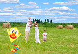 Happy family with pregnant wife fly a kite together in summer fi