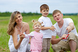 Happy family fly a kite together in summer field