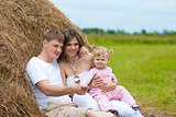 Happy family in haystack or hayrick