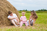 happy family sitting near haystack