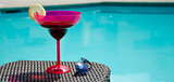 Drink and sunglasses by the pool