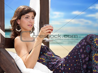 Young woman with a drink on the beach enjoying a cocktail.