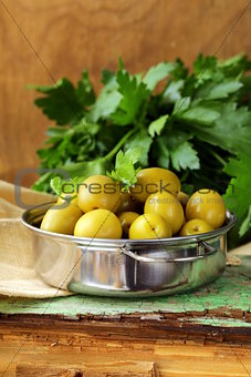 green  marinated olives with herbs  on a wooden table