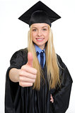 Closeup on smiling young woman in graduation gown showing thumbs