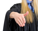 Closeup on woman in graduation gown stretching hand for handshak