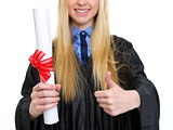 Closeup on young woman in graduation gown showing diploma and th