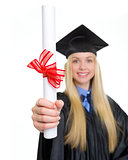 Closeup on diploma in hand of young woman in graduation gown