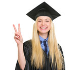 Happy young woman in graduation gown showing victory gesture