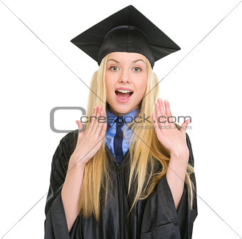 Surprised young woman in graduation gown