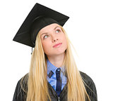 Young woman in graduation gown looking up on copy space