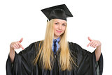 Happy young woman in graduation gown pointing down on copy space