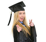 Smiling young woman in graduation gown pointing in camera