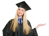 Happy young woman in graduation gown presenting something on emp