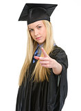 Concerned young woman in graduation gown threatening with finger