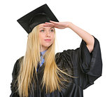 Young woman in graduation gown looking into distance