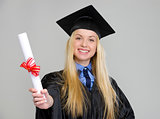 Smiling young woman in graduation gown showing diploma on grey b