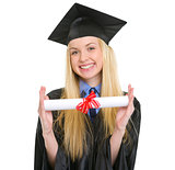 Smiling young woman in graduation gown showing diploma