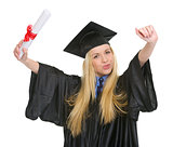 Happy young woman in graduation gown with diploma rejoicing succ