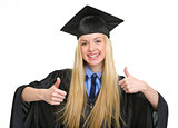 Happy young woman in graduation gown showing thumbs up