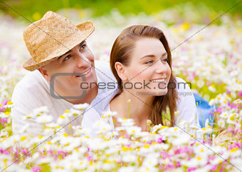 Beautiful couple on chamomile meadow