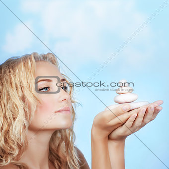 Pretty girl holding spa stones