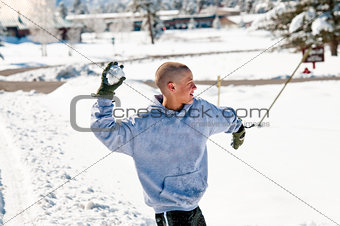 Bald boy throwing snowball