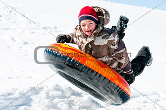 Boy up in the air on a tube in the snow