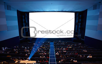 Cinema auditorium with people in chairs watching movie. Light of projector.