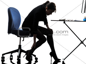 business woman massaging her leg silhouette