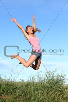 Blonde teenager girl jumping happy in the mountain