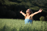 Beautiful teenager girl breathing happy in a green meadow