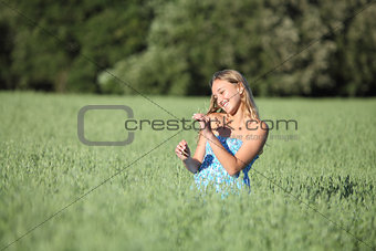 Beautiful teenager girl touching a oat stem