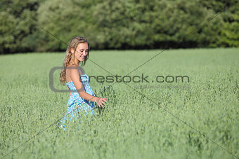 Beautiful teenager girl walking on a green oat meadow