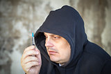 Drug addict men looks at the syringe in the hands