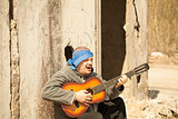 Man playing guitar leaning against wall