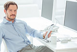 Handsome businessman sitting in front of monitors