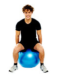 Handsome guy seated on exercise ball