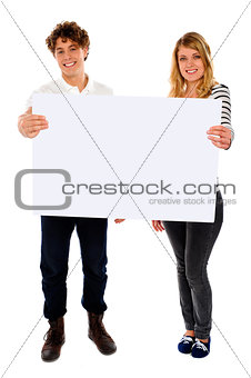Adorable young couple promoting blank banner ad